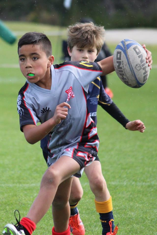 Boy running with rugby ball in rugby game