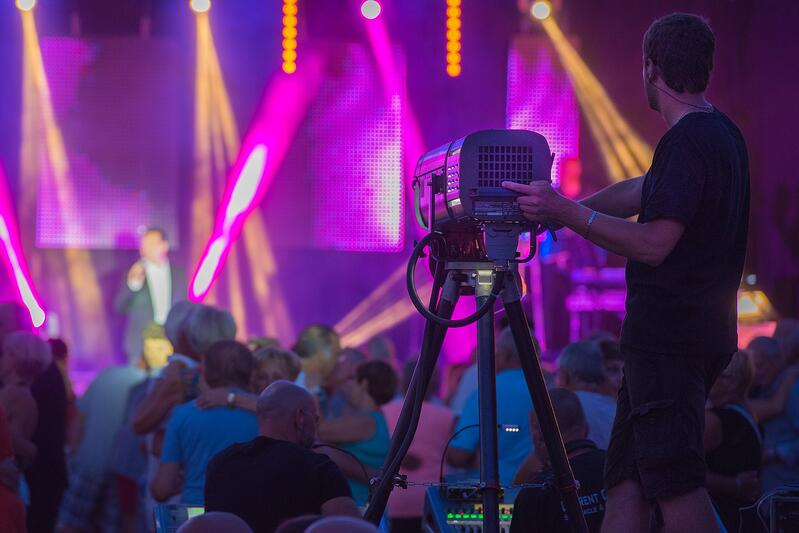 cameraman filming stage with a crowd of people