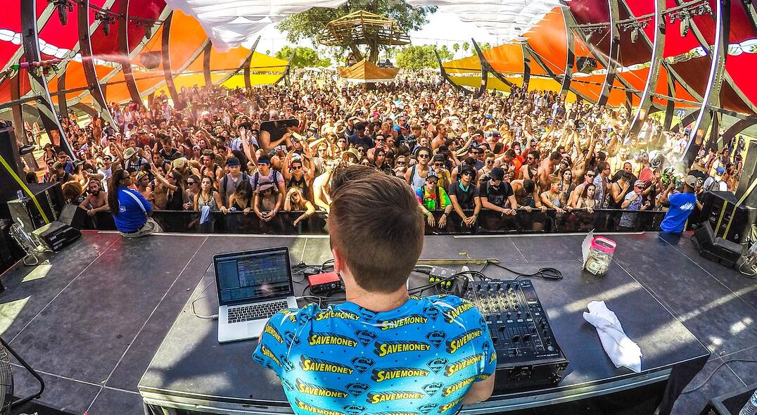 DJ playing decks on stage in front of a crowd at a music festival