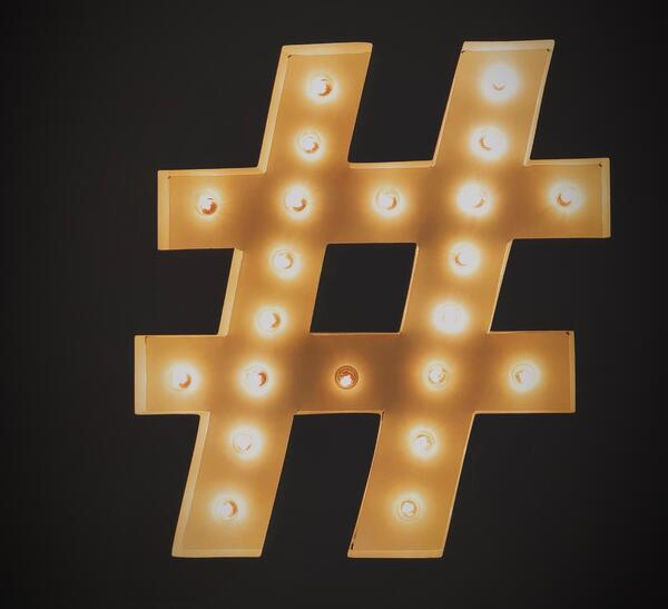 gold hashtag symbol with lights on against black background