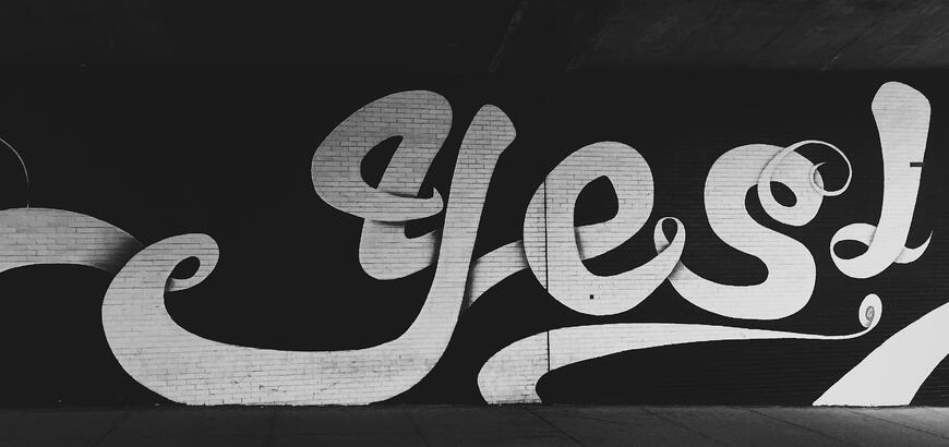 the word yes graffiti painted on a wall