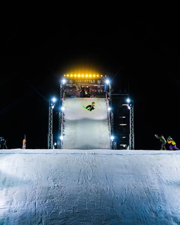 a snowboarder doing a jump at night time with people taking photos