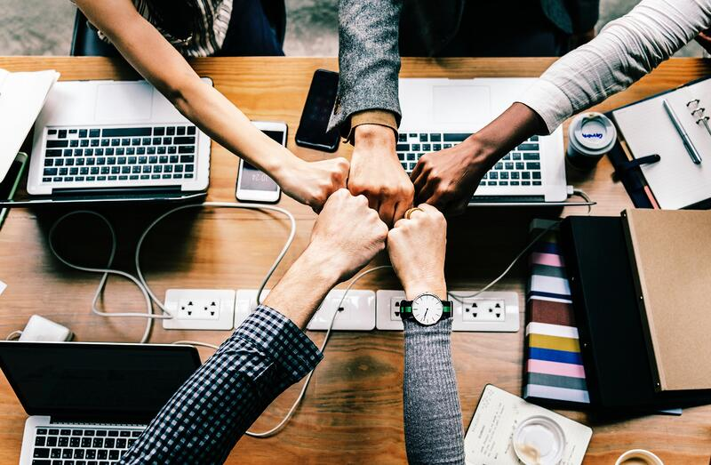 group of hands in middle over table with laptops and phones