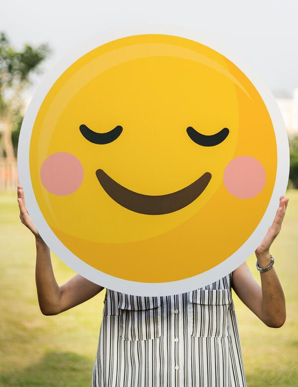 woman holding big cut out image of a smiley face emoticon