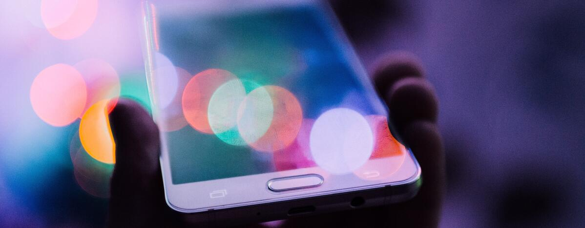 smartphone in hand with colourful lights