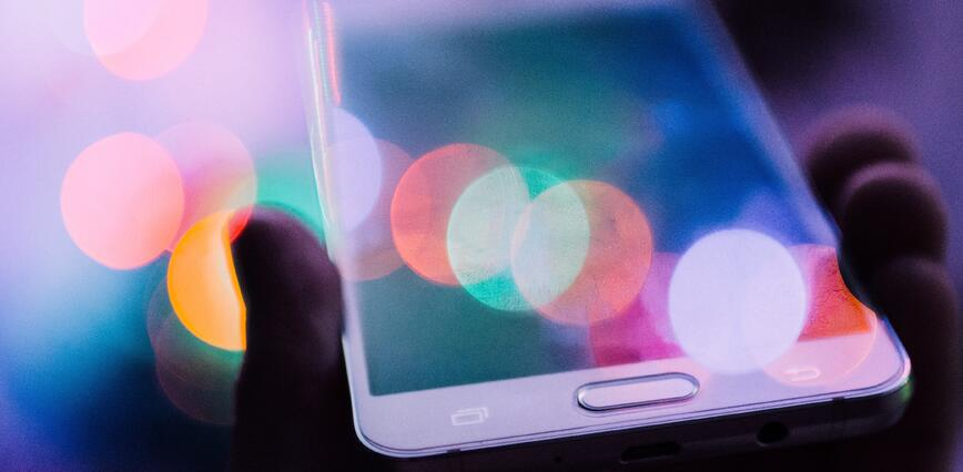 Smartphone in hand with multi-coloured lights