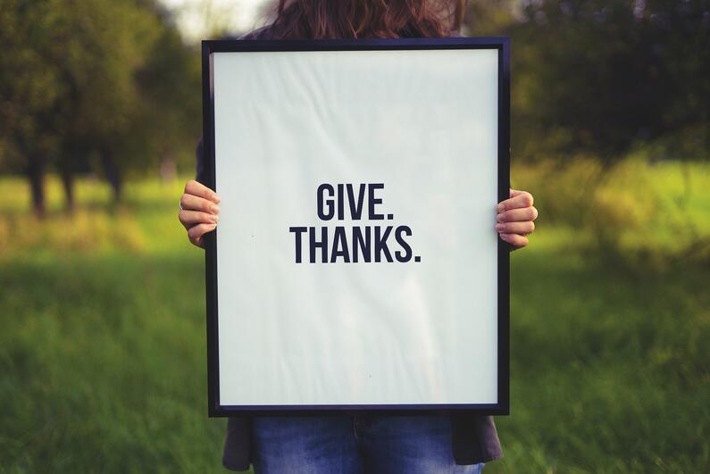 A poster that says 'Give thanks' held up in frame by woman in a  field