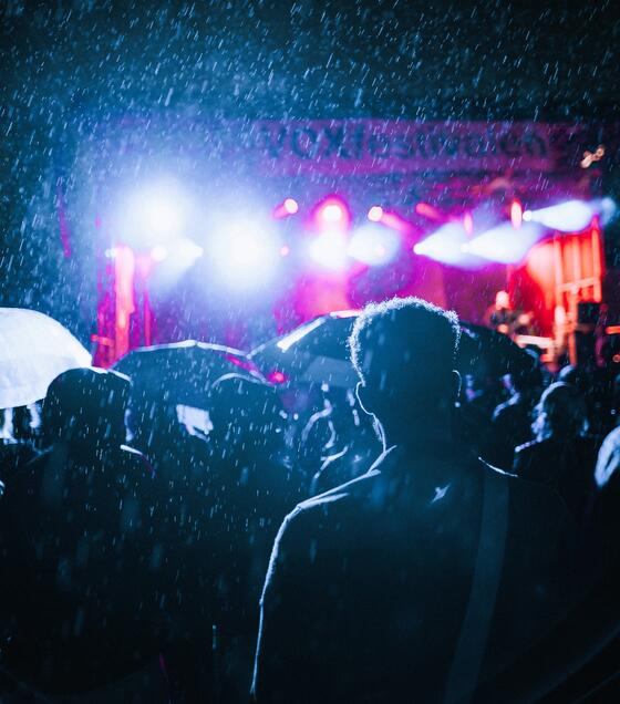 silhouettes of crowd at a festival at night in the rain