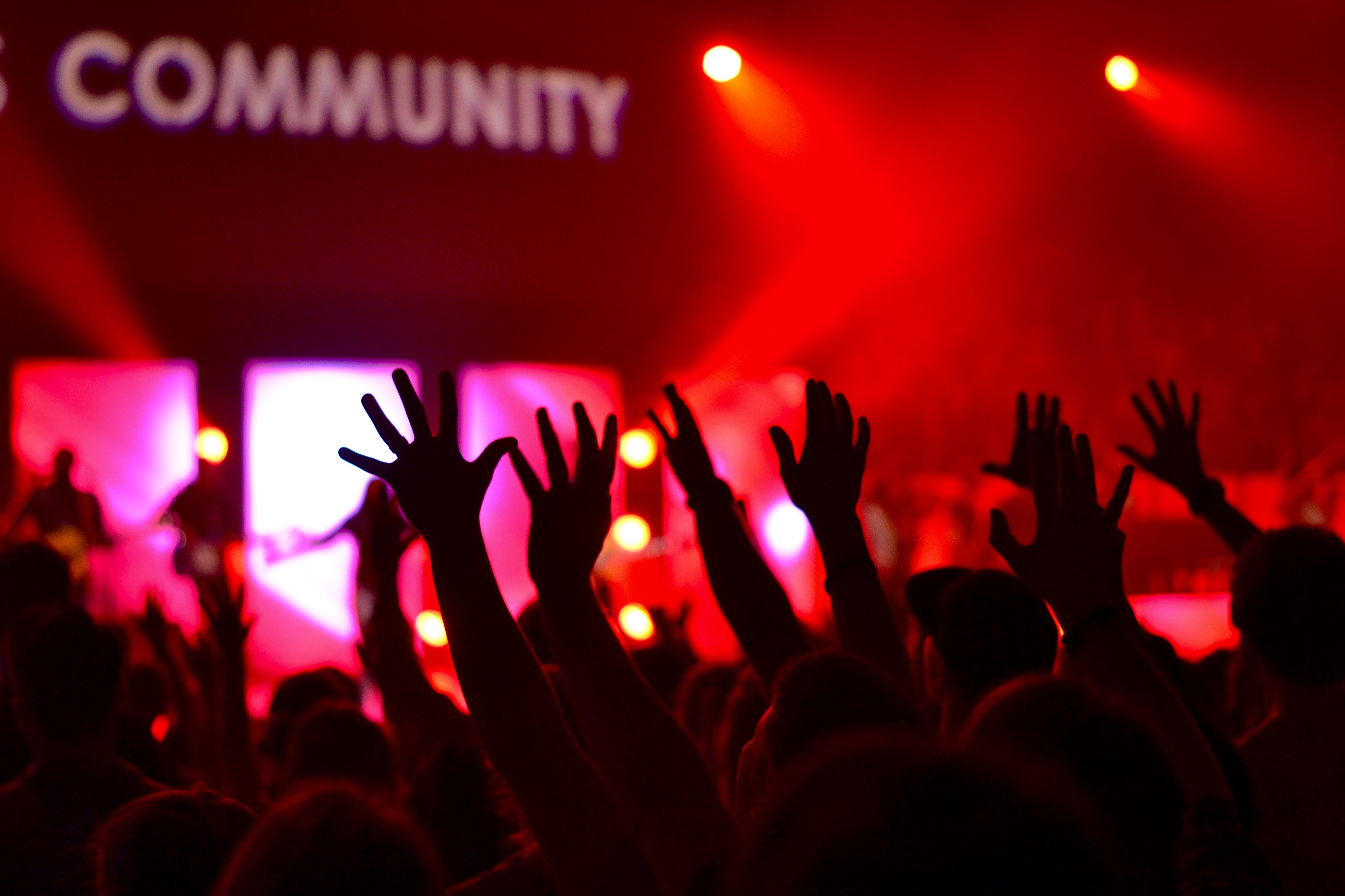 hands in the air at event with the word 'community' lit up